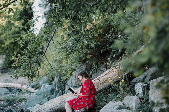 woman reading Bible along creek
