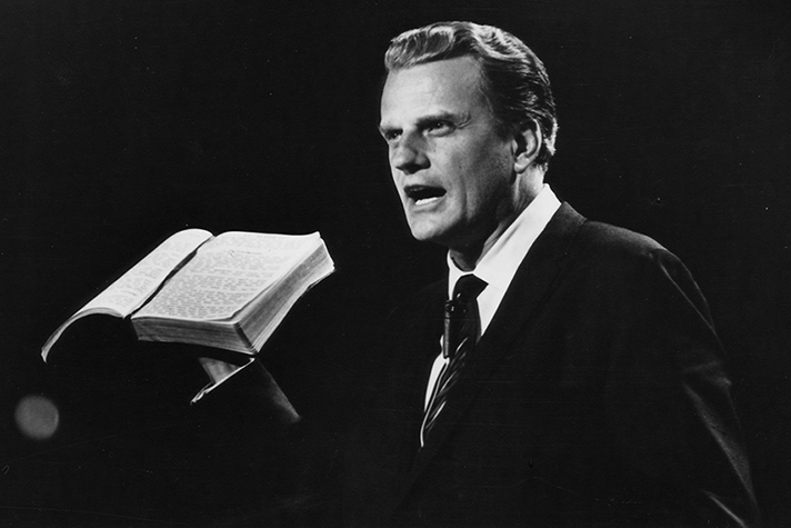Black and white photo of Billy Graham holding Bible