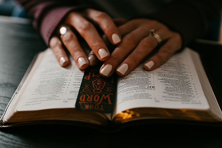 Person's hands on Bible