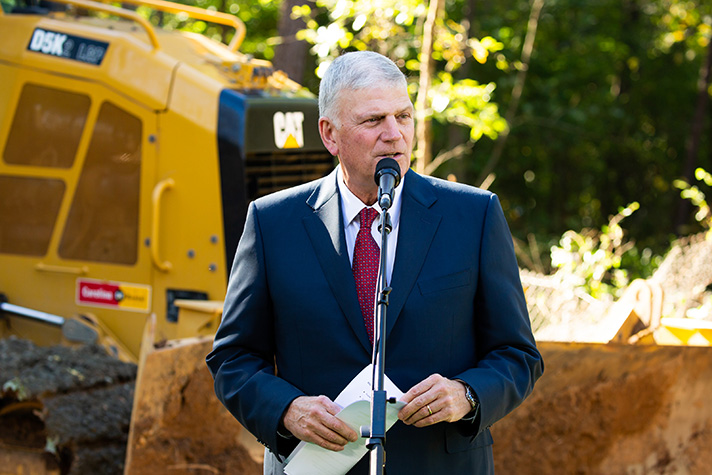 Franklin Graham talks in front of bulldozer