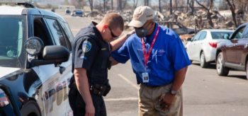 Chaplain praying with police officer after tornado