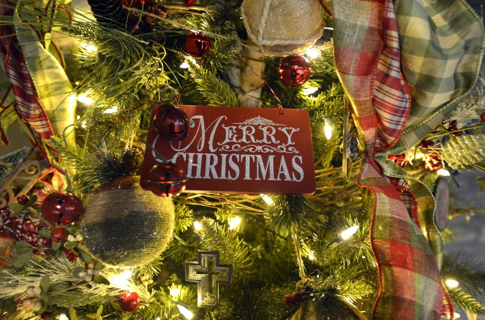 """Merry Christmas"" ornament hanging on a decorated Christmas tree"