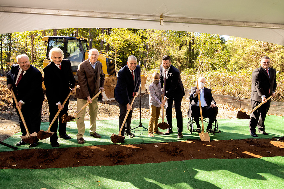 Men holding shovels, smiling, at groundbreaking