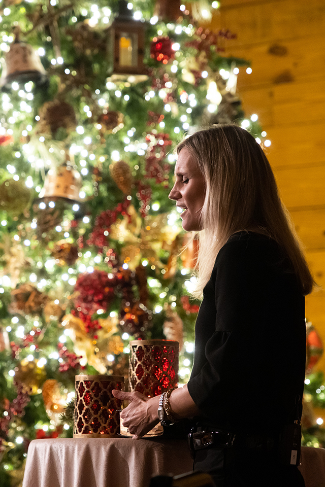 Rachel-Ruth Wright praying in front of lit Christmas tree