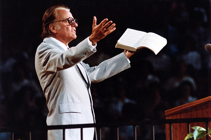 Billy Graham with Bible in hand, arms open, preaching
