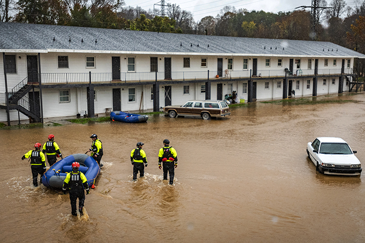 Rescuers in knee-deep water with raft outside apartments