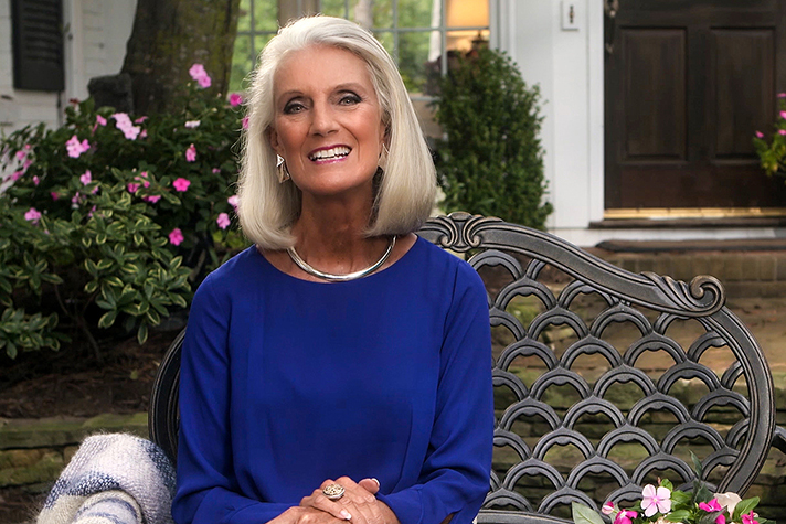 Anne Graham Lotz sitting on a bench in front of flowers