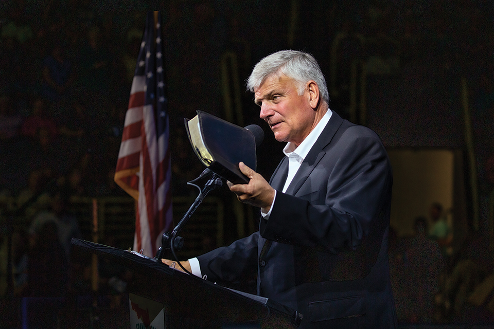 Franklin Graham holding a Bible at podium