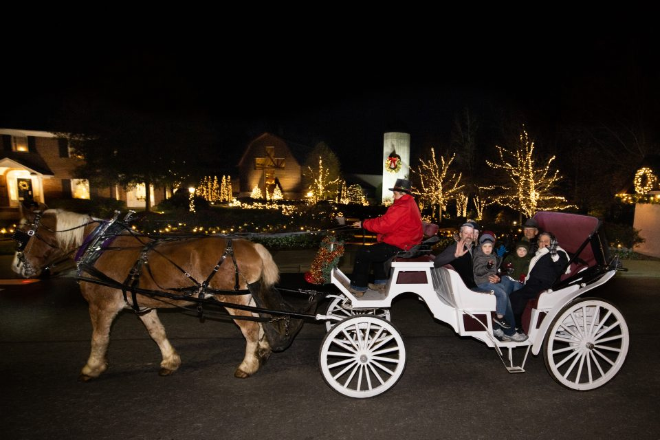 family waving from horse-drawn carriage