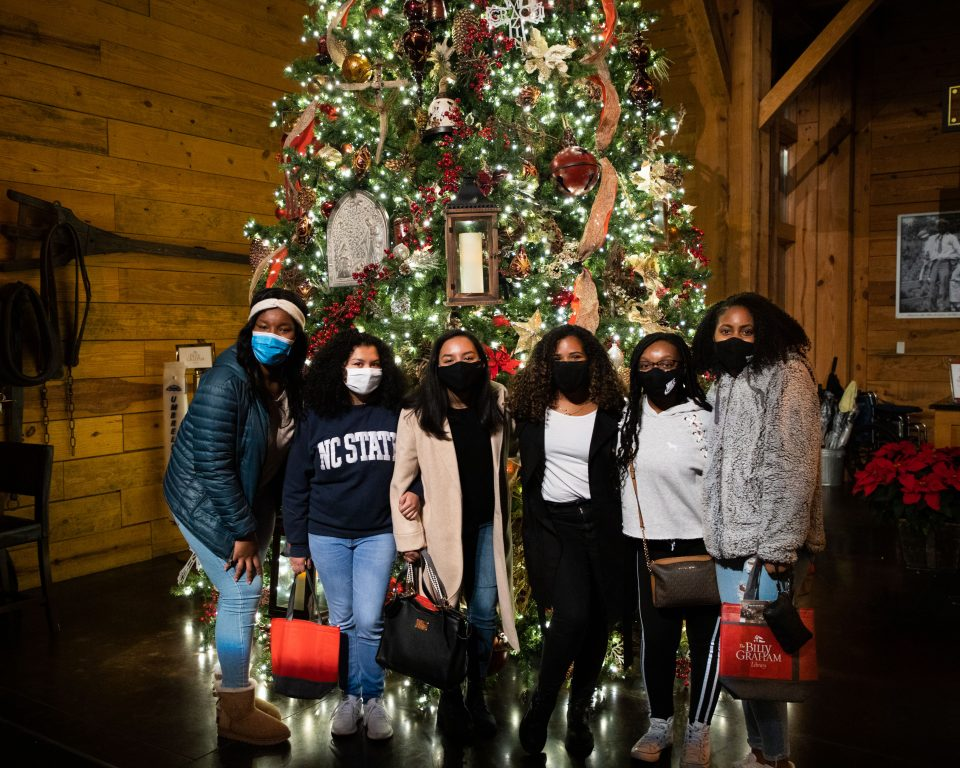 Six young women in front of large Christmas tree