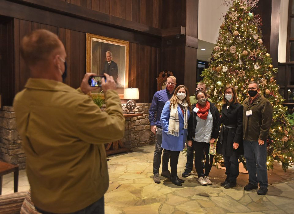 People having their picture taken in front of large Christmas tree
