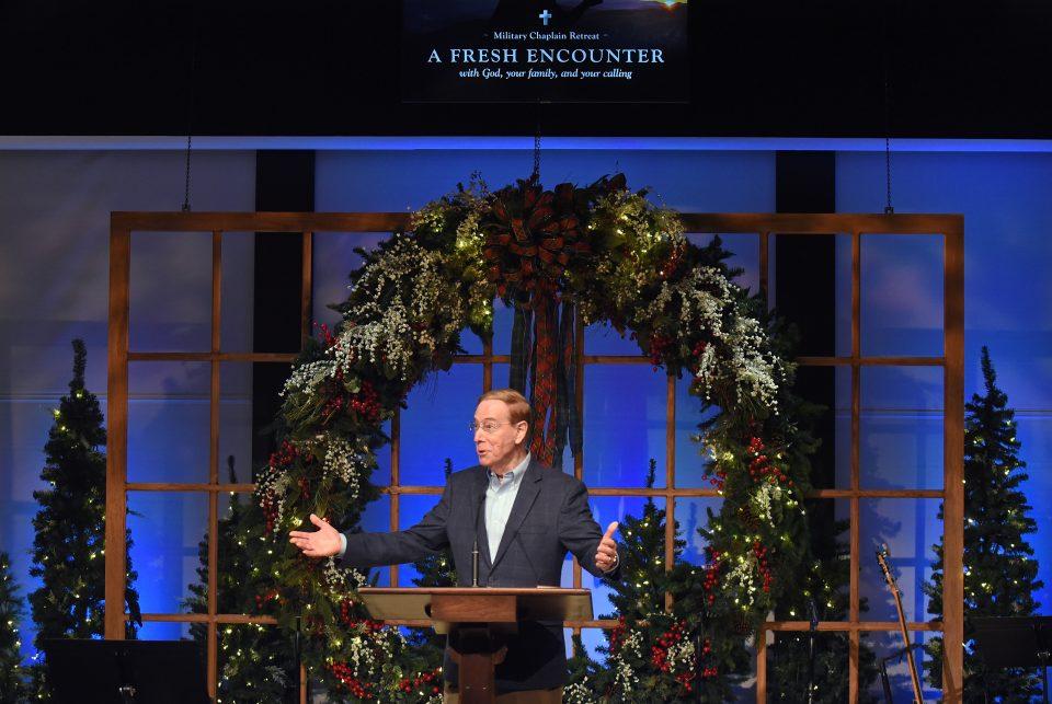 Dr. Gary Chapman at podium; large wreath