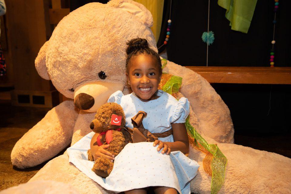 Little girl holding teddy bear and leaning against giant teddy bear