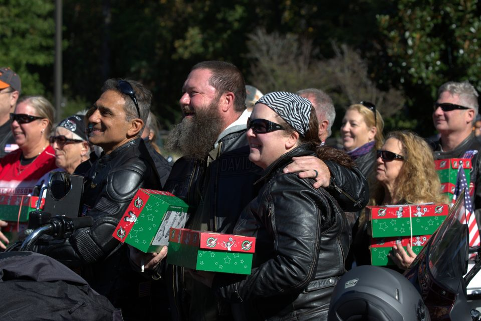 Bikers smiling and holding gift-filled shoeboxes