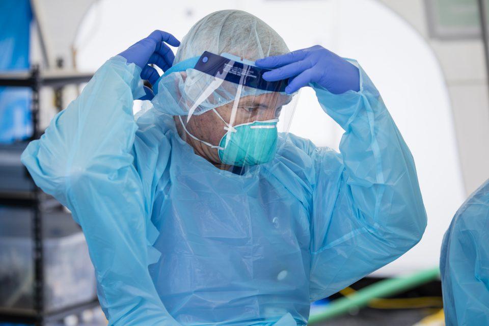 Medical staff adjusting face shield