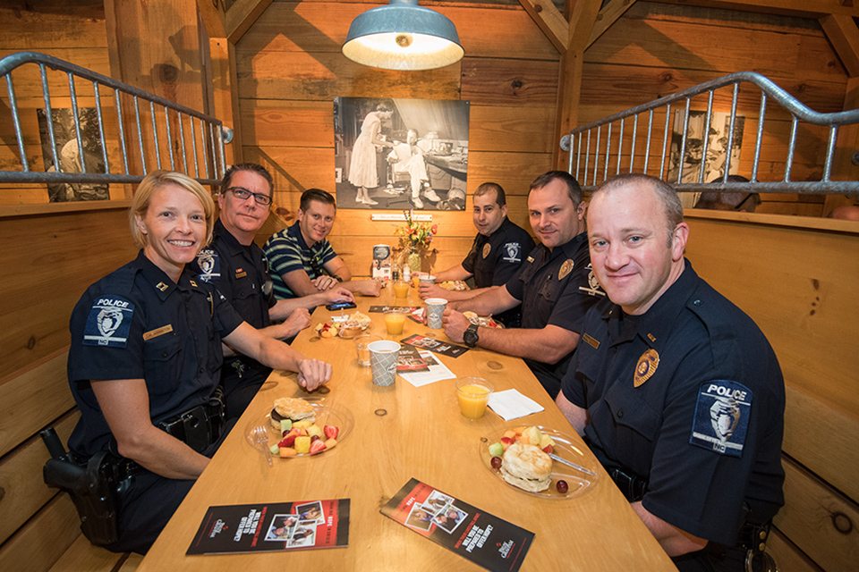 Officers sitting in booth smiling