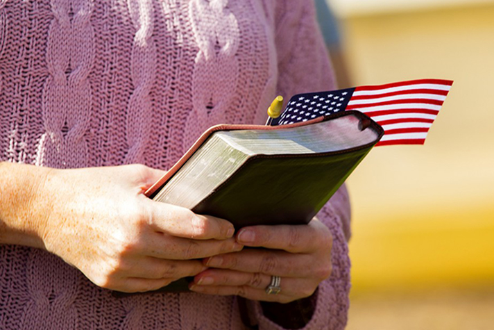 Woman's hands holding Bible and American flag