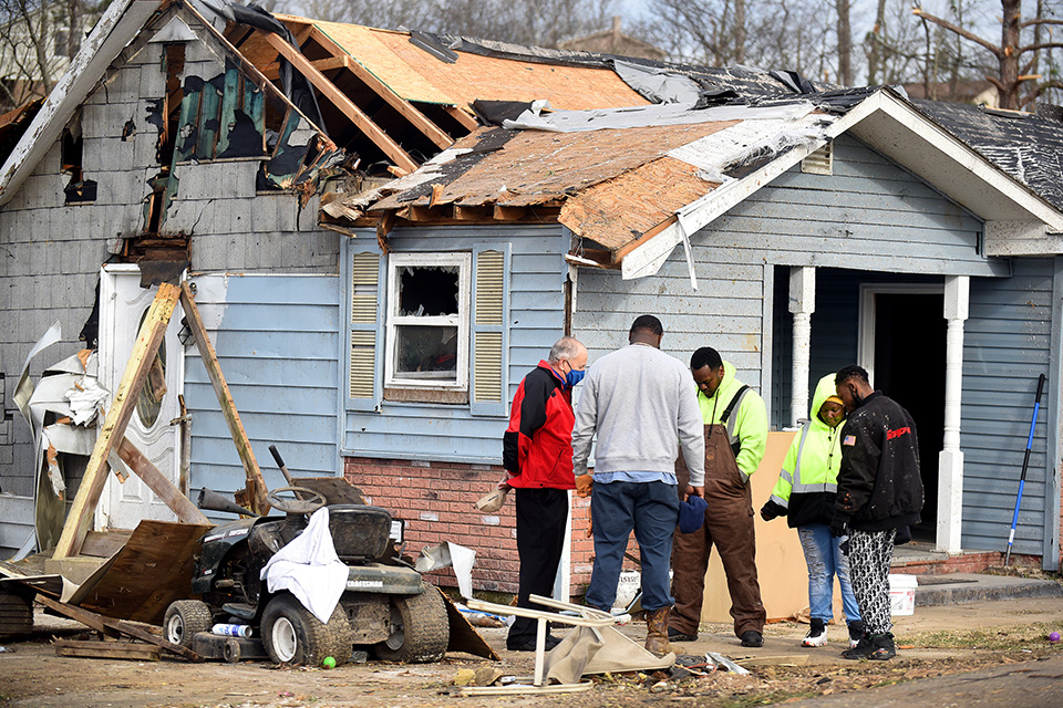 chaplain prays with locals circled in front of damaged home