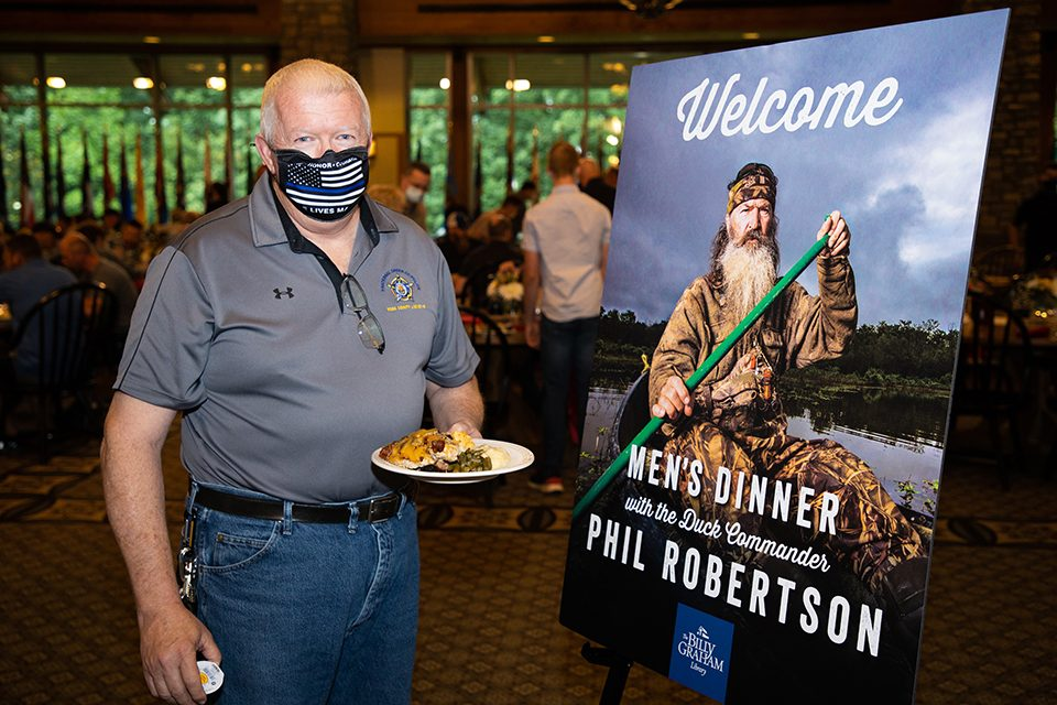 Man holding plate of food beside welcome sign