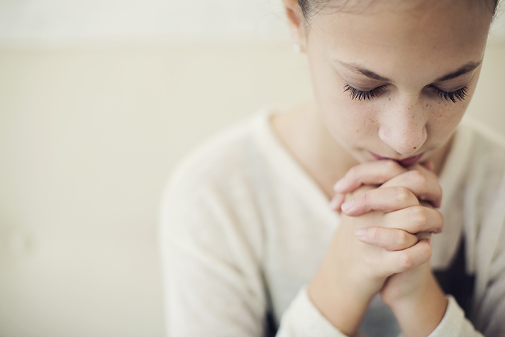Young girl with head bowed and hands folded, praying