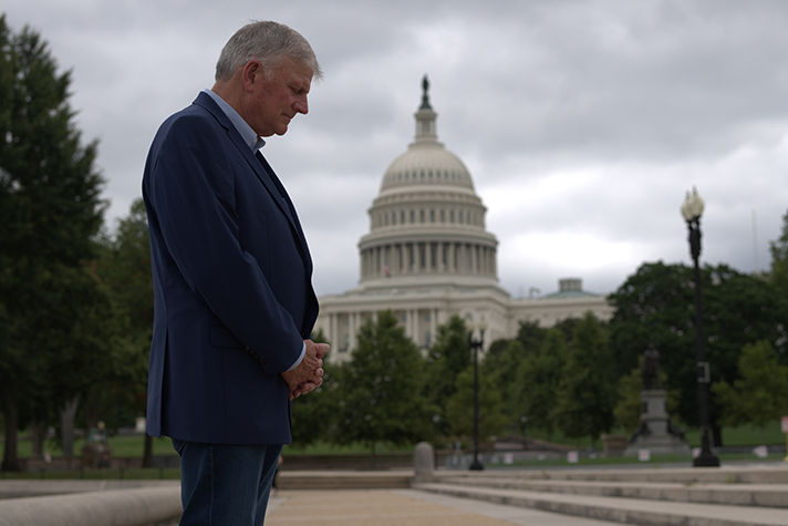 Franklin Graham prays with U.S. Capitol in background