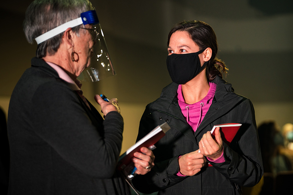 Two women talking, one wearing mask, one in face shield