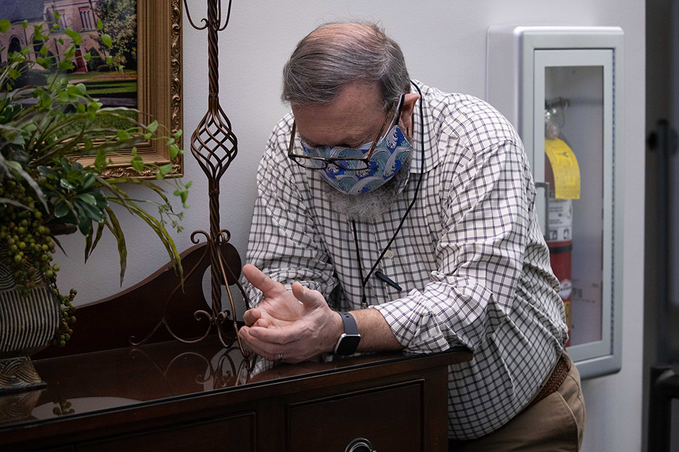 Man wearing mask, leaning on table to pray