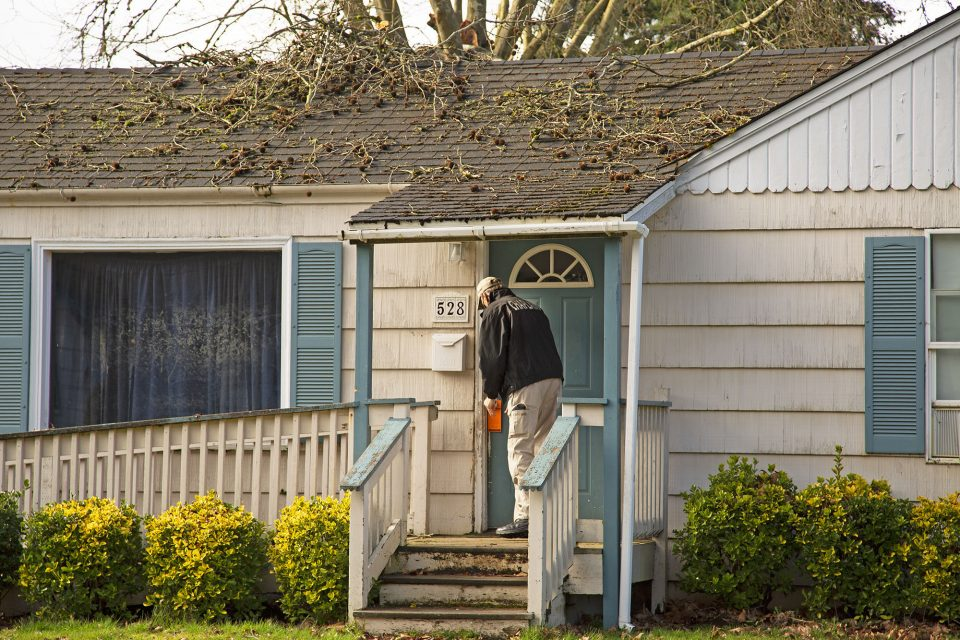 Chaplain knocking on door of house with debris on roof