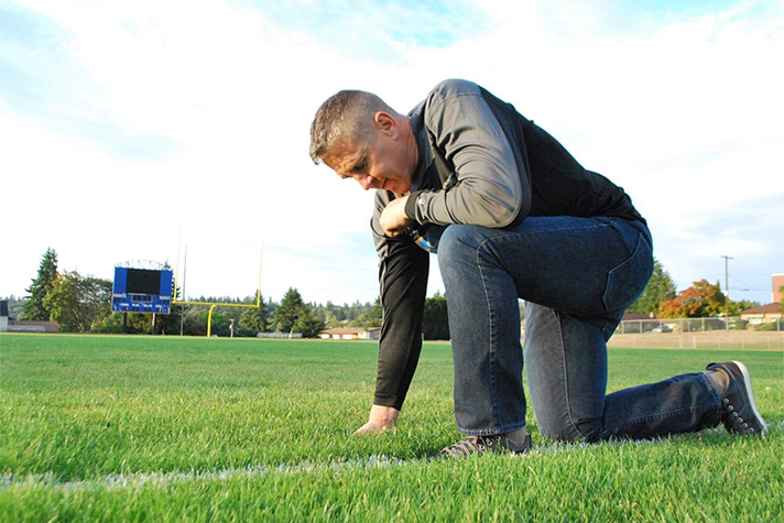 man taking a knee to pray on football field