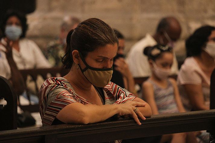 Woman with mask on praying with others in church