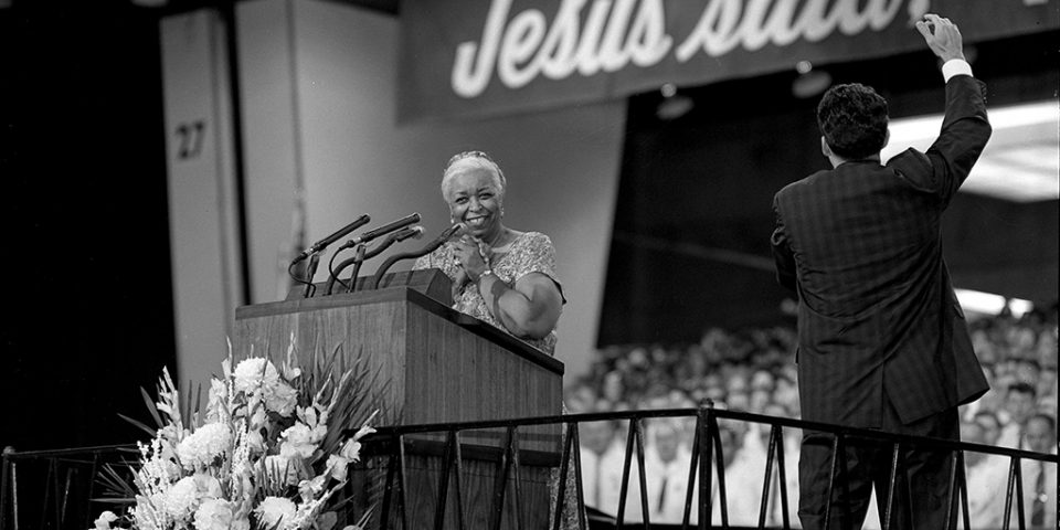 Black and white photo of Ethel Waters at lectern, smiling. Cliff Barrows raises an arm to direct the choir.