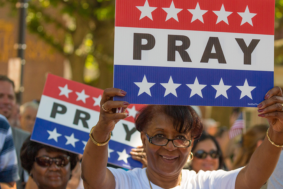 """Woman holding up red, white and blue sign that says """"pray."""""""