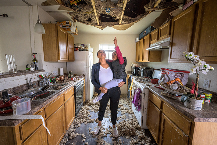woman holding child in destroyed kitchen