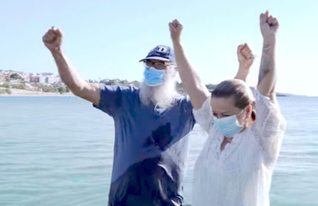 Pastor Salvori and Ana María stand in water, arms in air, after her baptism