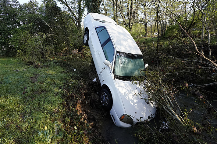 White car hood first into ditch
