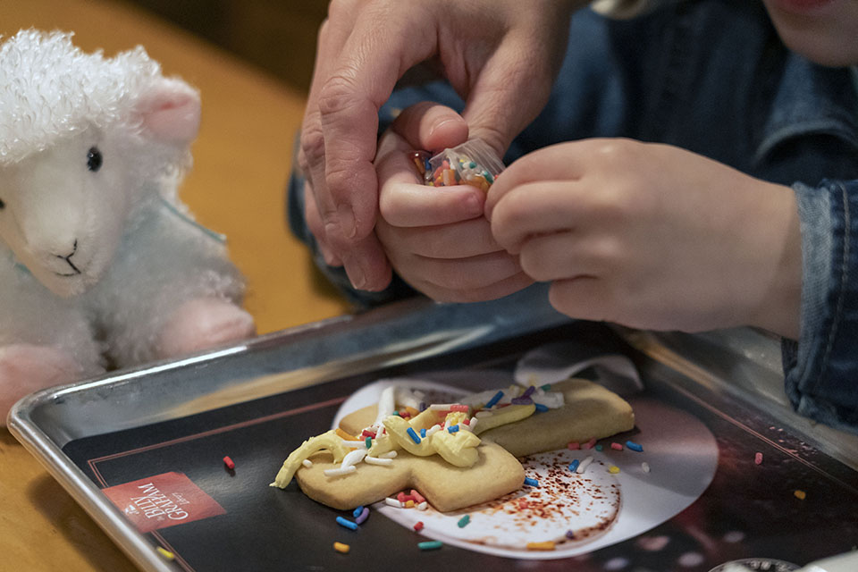 Adult helping a child's hands decorate a cookie