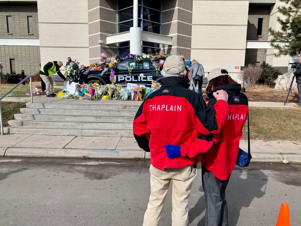 Chaplains hold each other at officers' memorial site