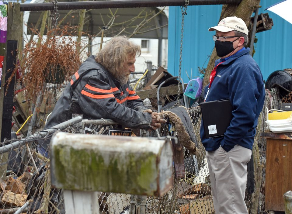 A chaplain talks to a local recovering from the flood
