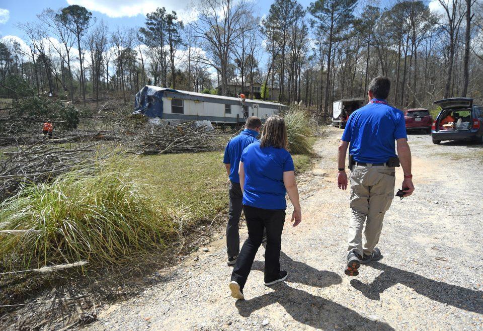 Chaplains walk on gravel road toward a home