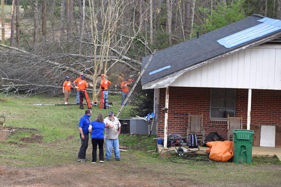 Team of volunteers stand in homeowner's yard