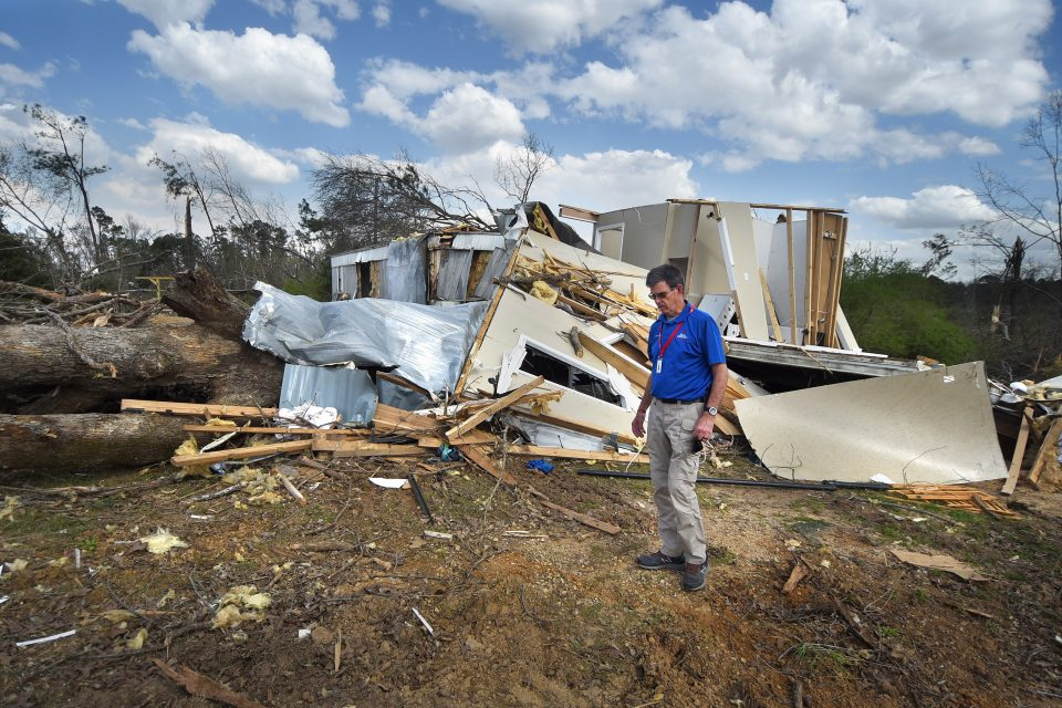 Chaplain stands in front of home that is falling apart