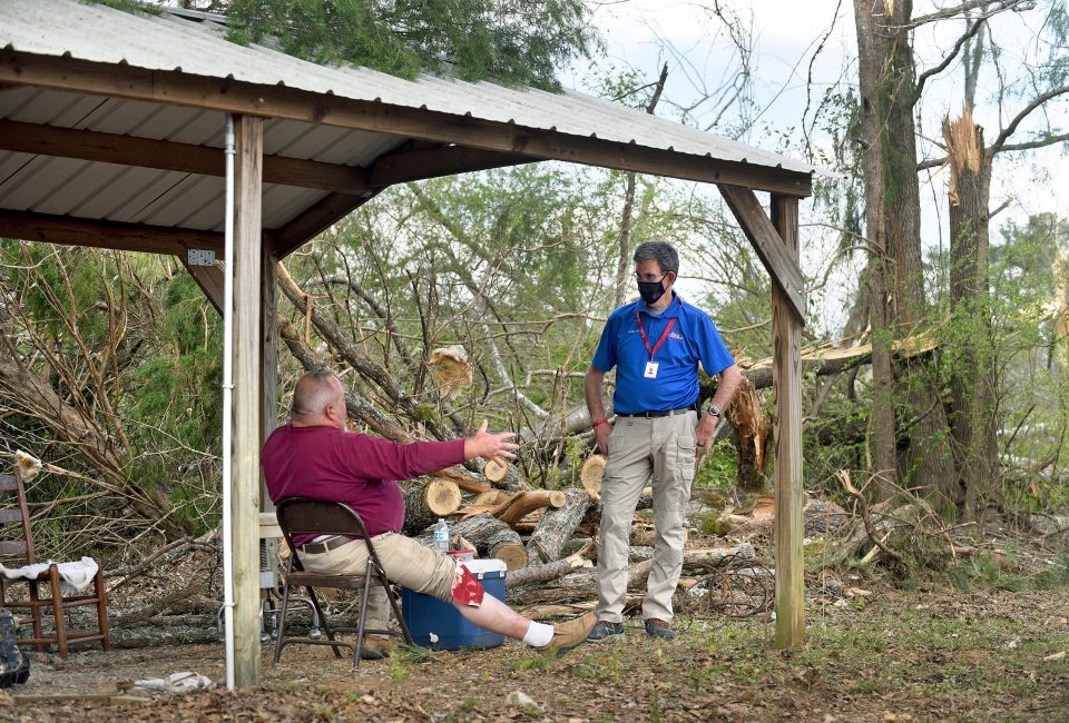 Chaplain speaks with man who is sitting with cloth on bloody knee, fallen trees in background