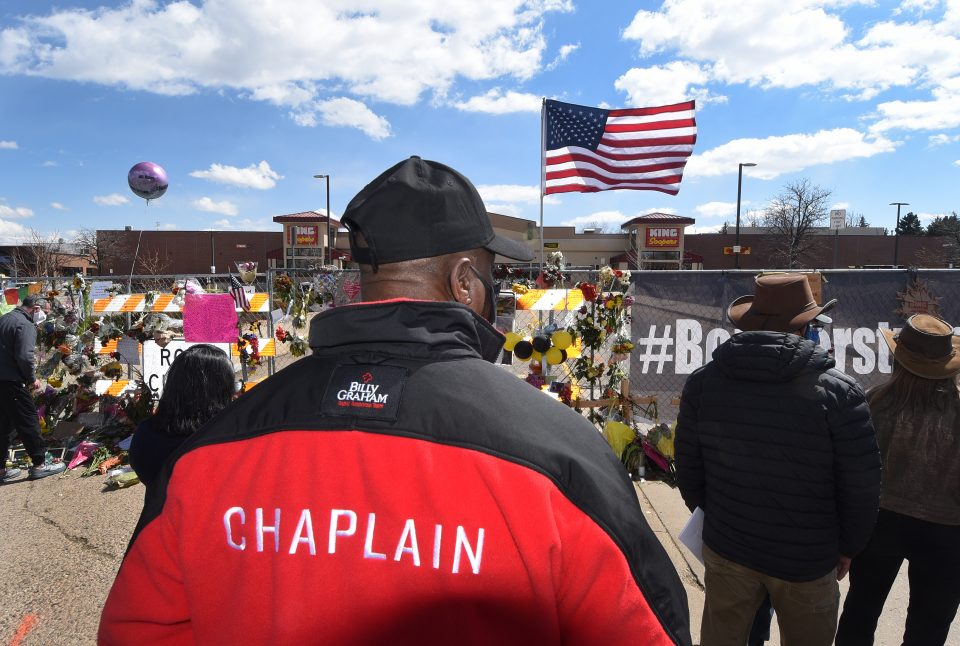 Chaplain with back to camera, looking at memorial