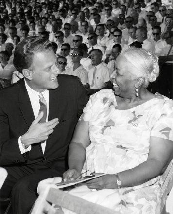 Billy Graham kneels down beside Ethel Waters, smiling.