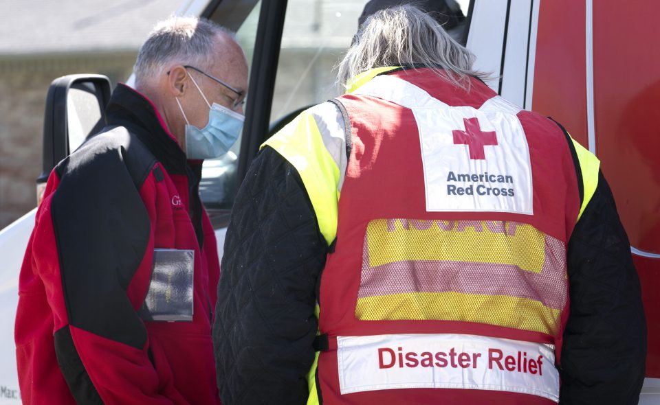 A chaplain prays with an American Red Cross worker