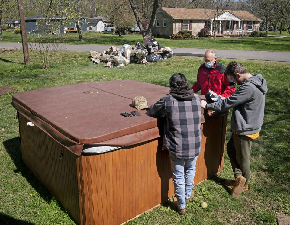 Two young men talk with a chaplain by a hot tub that moved during the flood
