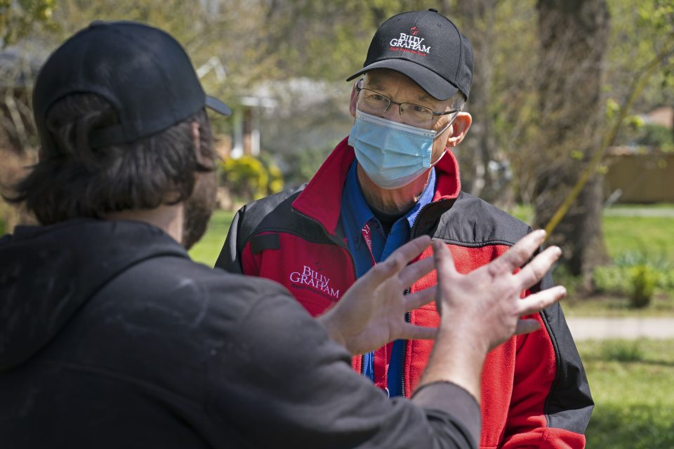 A man uses his hands to describe what happened during the storm when talking to a chaplain