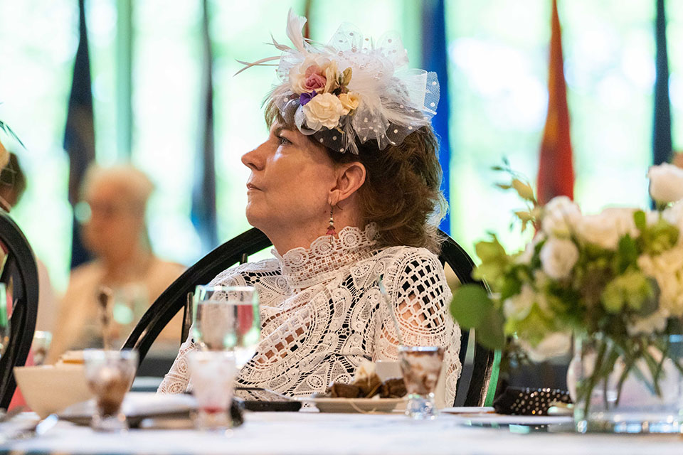 Woman with fancy side hat sits and listens