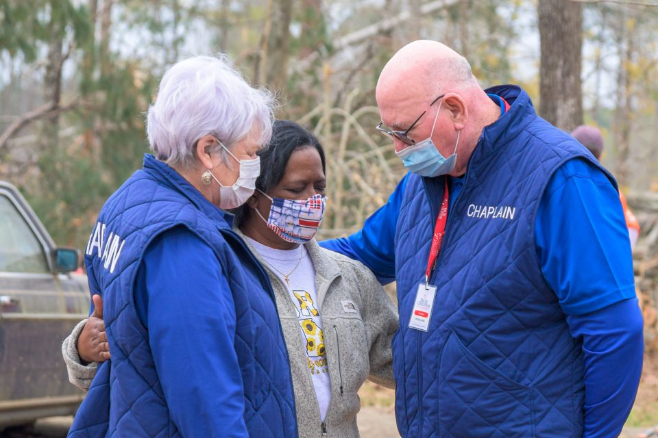 Chaplains pray on either side of a masked woman