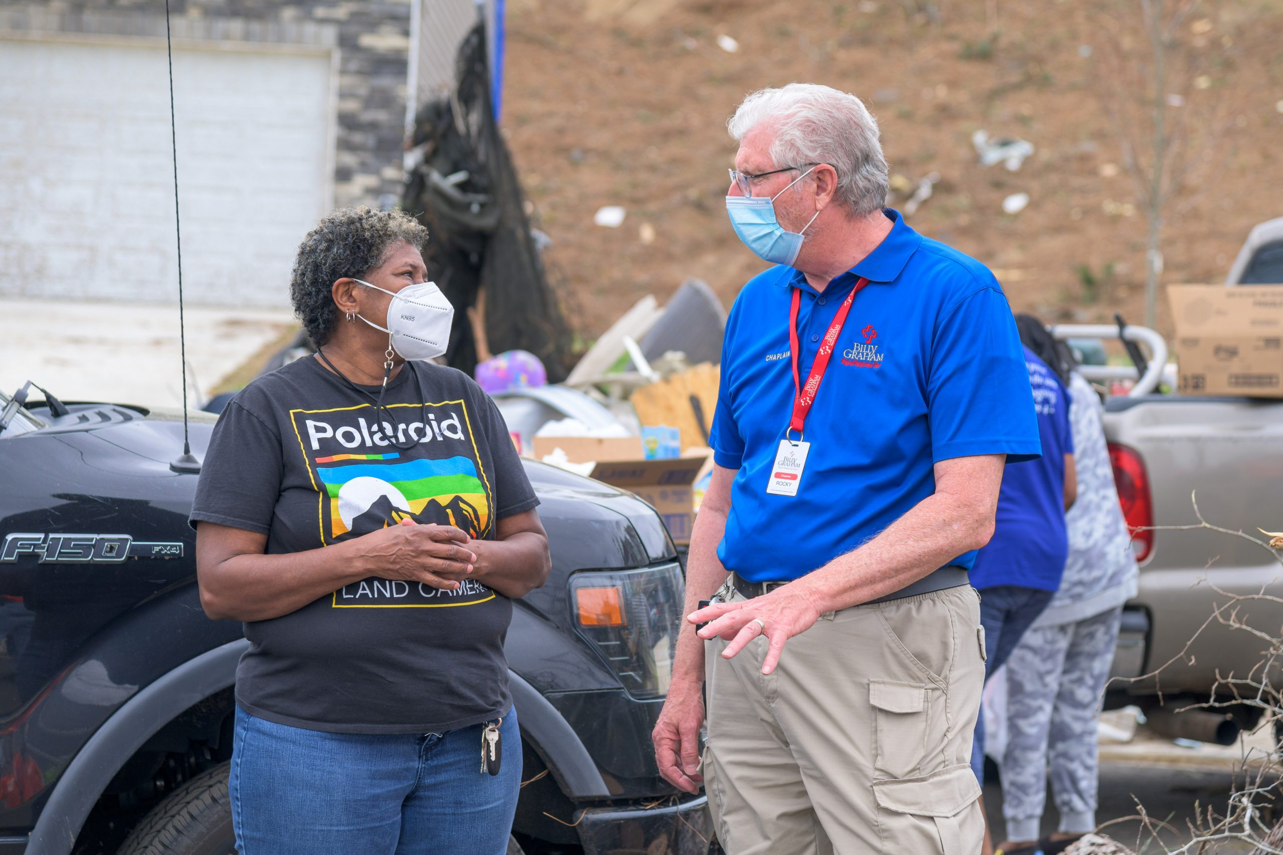 A chaplain talks with a smiling masked woman